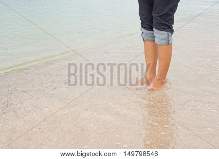 barefoot legs walking in the seashore Vacation on summer sea beach