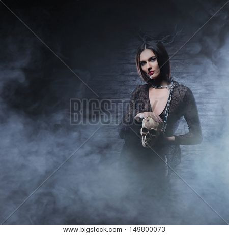 Halloween concept: young and sexy witch in the dungeon