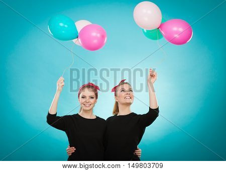 Memory of childhood and forgotten dreams. Two cute lovely retro styled women behave like little girls. Adults trying to fly away by balloons to dream come true.