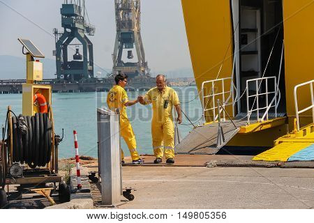 Piombino Italy - June 30 2015: Corsica Express workers prepare a gangway for the exit of passengers in the seaport