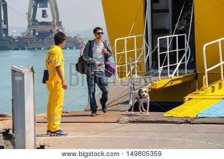 Piombino Italy - June 30 2015: Man with dog coming out of the ferry boat Corsica Express in the seaport