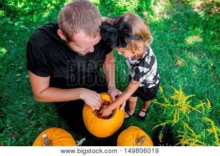 Daughter And Father Pulls Seeds  Fibrous Material From A Pumpkin Before Carving For Halloween. Prepa