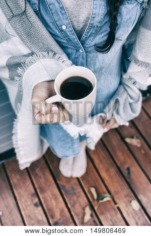 Close up view from above of woman covered in blanket holding cup of coffee. Wooden patio deck with fall leaves as the background