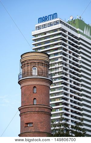 Luebeck Travemuende Germany - September 30 2016: Old and new landmarks historic lighthouse and the high rise hotel maritim in Travemuende a popular seaside resort on the beach of the Baltic Sea