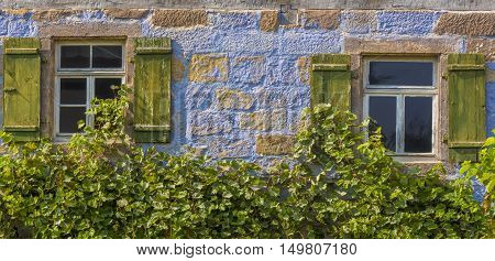 Architecture background from a blue german house - Blue painted german house facade with two old wooden windows and shutters partially covered with grape vines