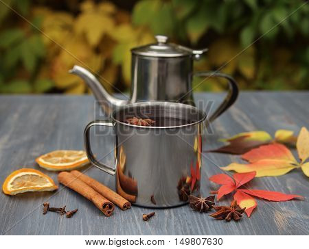 mulled wine in a metal mug with autumn leaves on a table in a garden