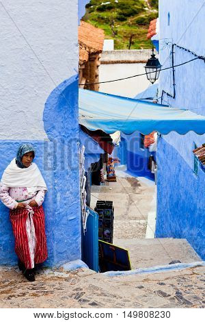 Muslim Woman Standing On The Street In Ancient Blue Medina In Chefchaouen, Morocco