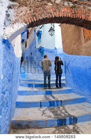 CHEFCHAOUEN, MOROCCO - JANUARY 2, 2014: Tourists walking in beautiful blue medina of Chefchaouen city in Morocco North Africa