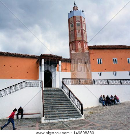 CHEFCHAOUEN, MOROCCO - JANUARY 2, 2014: People resting on the square nearby Grand Mosque in Medina of Chefchaouen. Noteworthy for its unusual octagonal tower the Grande Mosque was built in the 15th century.