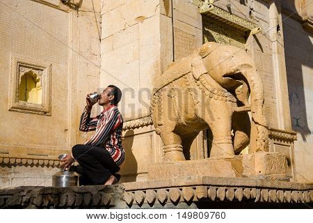 Jaisalmer India - 2015 January 7 : The guard of the Salim Singh Ki Haveli in the historic center of Jaisalmer drinking from a cup next to the entrance with an elephant sculpture