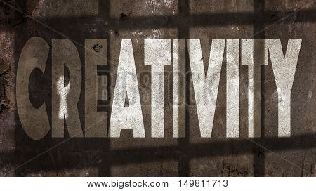 Creativity Written On A Wall With Jail Bars Shadow.