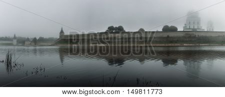 panorama of the river and Pskov Kremlin in the fog on a grey background