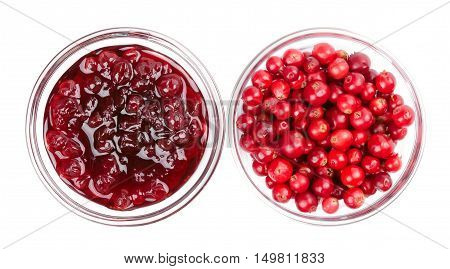 Lingonberry jam and lingonberries in glass bowls over white. Fresh red fruits of Vaccinium vitis-idaea, also mountain cranberries, partridgeberries or cowberries. Staple food in Scandinavian cuisine.