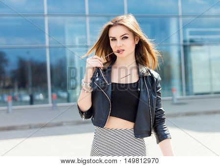 Girl model outdoor portrait holding glasses leather jacket and skirt. Glamour stylish bombshell. Young fashion lady with long brown hair wear cool outfit and sunglasses. Glass building in background.