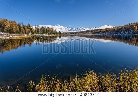 Bright picturesque autumn landscape with a beautiful lake forest snow covered mountains and their reflections on a background of blue sky on a sunny day