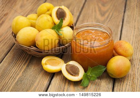 Fresh apricot jam in a jar with mint and apricot fruits on wooden table