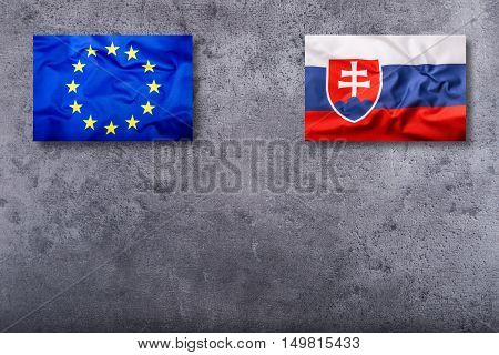 Flags of the Slovak Republic and the European Union on concrete background.