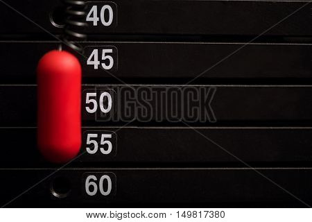 More weight. Close up of a metal weight stack with a red plastic pin showing the amount of weight