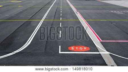 Airfield runway and taxiway with marking and signs.