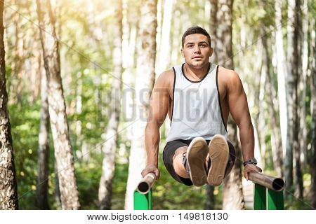 Workout in the park. Handsome athletic serious man leaning on parallel bars and stretching his legs forward while holding his body in the air