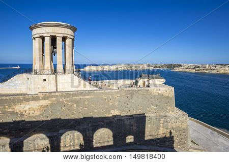 Valletta Malta - Siege Bell War Memorial at the Grand Harbor of Valletta with tourists and clear blue sky