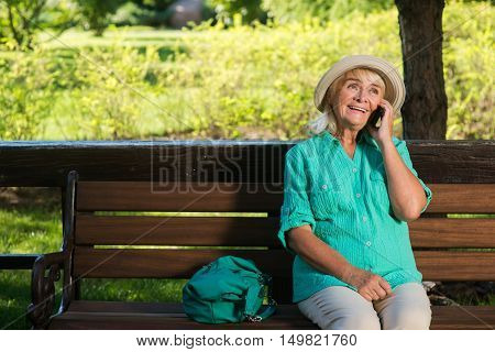 Lady with phone is smiling. Senior lady sits on bench. Lowest prices for outcoming calls. Always stay in touch.
