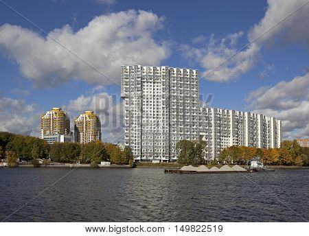 The big white house on the embankment of the river in autumn.