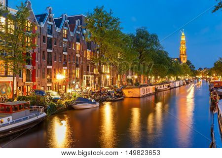 Night city view of Amsterdam canal Prinsengracht with houseboats and Westerkerk church, Holland, Netherlands.