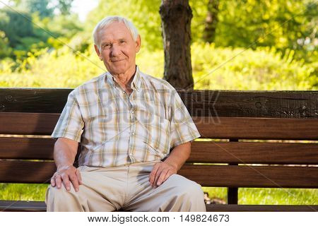 Old man sits on bench. Elderly guy is smiling. He deserves a good rest. All problems left behind.
