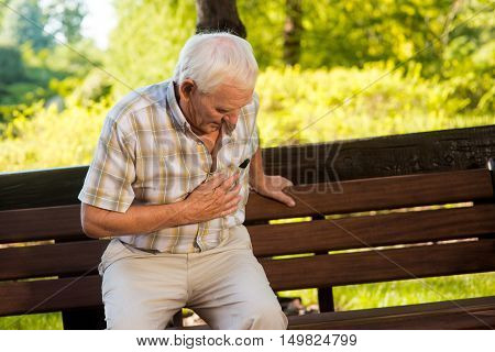 Old man holding his stomach. Senior male near park bench. Constant pain under ribs. Problems with health.