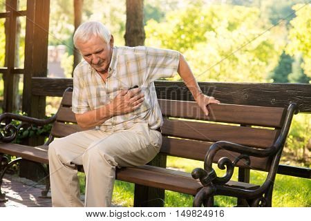 Senior guy has heartache. Elderly man on park bench. Too much stress. Chronic disease of heart.
