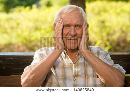 Elderly man has headache. Old guy holds his head. High blood pressure and temperature. How stress impacts health.