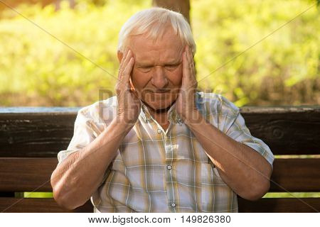 Old man holding his head. Elderly person has headache. Health is in danger. Discomfort grows into pain.