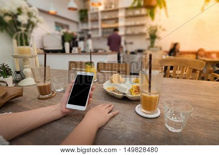 Weekend lifestyle scene of young woman using phone in cafe. Trendy lifestyle with wireless digital technology concept
