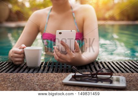 Vacation lifestyle morning scene of young woman using mobile phone while holding coffee cup in swimming pool. Weekend and holiday lifestyle with phone addict concept