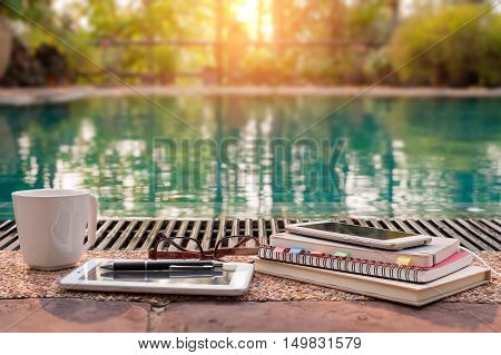 Abstract scene of notebooks tablet pc mobile phone glasses and coffee cup are put down beside swimming pool in morning time. Freelance working concept