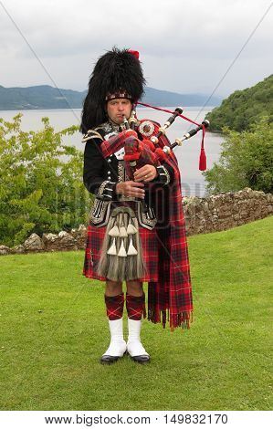 URQUHART CASTLE SCOTLAND UK - CIRCA AUGUST 2015: Scottish bagpiper dressed in traditional red and black tartan dress