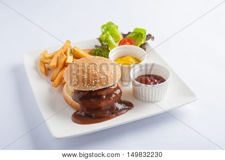 American style barbecue pork burger set including french fries ketchup mustard sauce garnished with fresh vegetables in caramic dish isolated on white background with clipping path