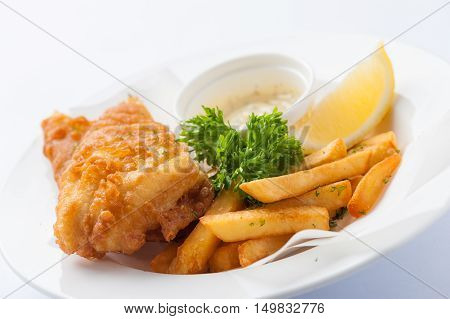 Traditional British style fish and chips including deep fried cod french fries lemon and tartar sauce in ceramic dish
