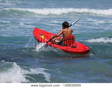 boy rowing in sea kayak.