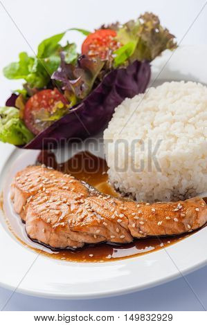 Fusion food style grilled salmon dressed with Japanese sweet sauce (Teriyaki) including Thai rice garnished with vegetables in ceramic dish