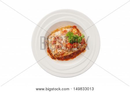 Top view of Traditional style Italian cuisine beef lasagna garnished with parmesan chesse parsley and tomatoes in ceramic dish isolated on white background