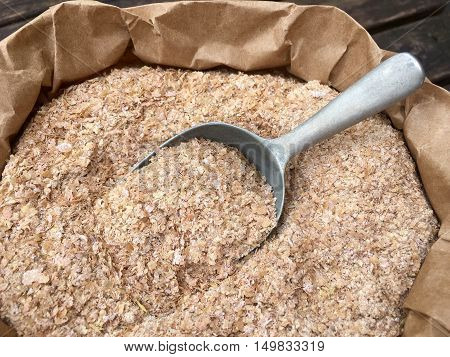 Wheat bran with a shovel made of metal in a brown paper bag