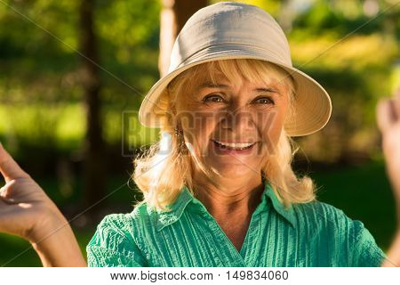 Portrait of smiling senior woman. Joyful lady in a hat. Feeling happier than ever. World will smile back.