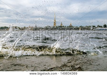 Saint-Petersburg.Russia.September 3 2016.Splashing waves on the river Neva and view of Peter and Paul fortress in Saint-Petersburg. poster