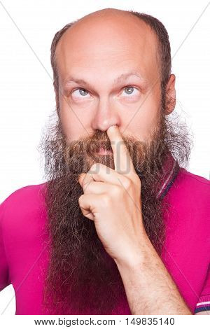 Portrait of a young blad bearded man with his finger in his nose isolated on white background.