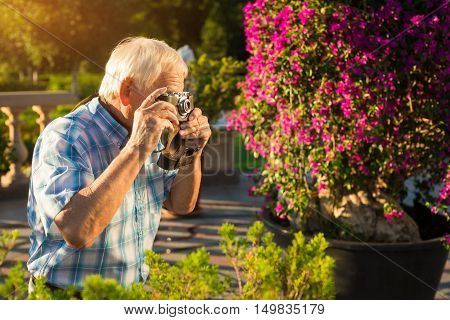 Senior man holding camera. Elderly male outdoors. Make few more pictures. Nature inspired photographer.