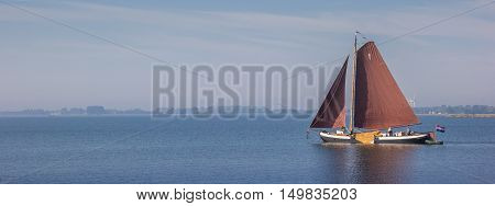 HOORN, NETHERLANDS - SEPTEMBER 13, 2016: Panorama of an old wooden sailing boat on the Ijsselmeer near Hoorn, Netherlands