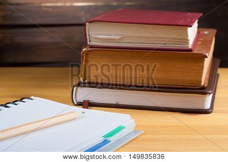 Notepad In The Box With A Pen And Glasses On A Wooden Table In The Background Of A Stack Of Books.