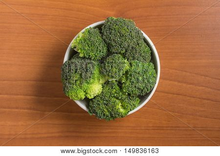 Fresh Brocolli into a bowl over a wooden table